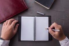 Vista superiore delle mani dell'uomo che scrivono sul taccuino vuoto con la penna nell'ufficio fotografie stock libere da diritti