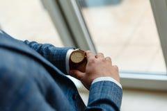 Vista superiore delle mani di un uomo in un vestito che esamina un orologio L'uomo d'affari sta controllando il tempo sul suo oro fotografia stock