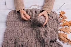 Vista superiore delle mani di una donna che tengono una palla del filato di lana su una linguetta Immagini Stock Libere da Diritti