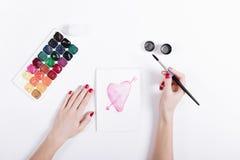 Vista superiore delle mani di una femmina con tiraggio rosso del manicure l'acquerello fotografia stock libera da diritti