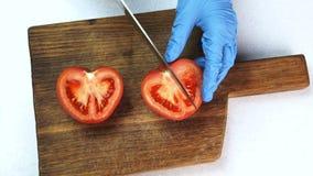 Vista superiore delle mani in guanti a bordo del taglio con il pomodoro del coltello orribile archivi video