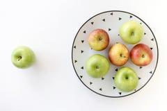 Vista superiore delle mele rosse e verdi in piatto bianco con il modello nero dei triangoli ed in mela verde su fondo bianco Fotografia Stock