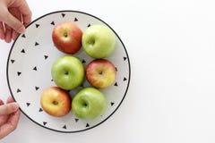 Vista superiore delle mele rosse e verdi in piatto bianco con il modello nero dei triangoli con le mani dalla parte di sinistra c fotografia stock libera da diritti