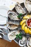 Vista superiore delle ostriche fresche e di molti generi di ostriche fresche servite in vassoio rotondo con il limone della fetta fotografia stock