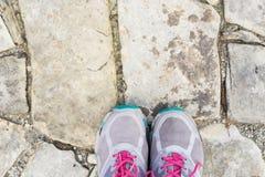 Vista superiore delle paia delle scarpe delle scarpe da tennis sulla pietra per lastricati Fotografia Stock