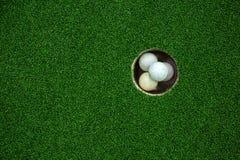 Vista superiore delle palle da golf impilate su nel campo verde Fotografie Stock
