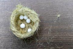 Vista superiore delle pillole omeopatiche nel piccolo nido della iuta su fondo di legno vago Un concetto di omeopatia fotografia stock libera da diritti