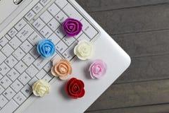 Vista superiore delle rose colourful e del computer portatile bianco immagini stock libere da diritti