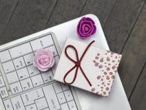 Vista superiore delle rose, del computer portatile bianco e del contenitore di regalo rosso su fondo fotografia stock libera da diritti