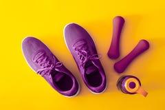 Vista superiore delle scarpe di sport, delle teste di legno e della bottiglia porpora e viola di acqua su fondo giallo Forma fisi fotografia stock libera da diritti