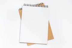 Vista superiore dello scrittorio bianco con il taccuino in bianco nel mezzo Fotografia Stock