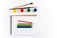 Vista superiore dello sketchbook, dei pennelli, dei pensils variopinti e delle pitture di gouache Fotografia Stock Libera da Diritti