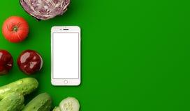 Vista superiore dello smartphone con lo schermo in bianco e le verdure crude fresche sulla tavola verde illustrazione 3D Immagini Stock
