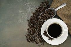 Vista superiore di caffè caldo nella tazza bianca con i chicchi, la borsa ed il mestolo di caffè dell'arrosto sul fondo di pietra immagine stock libera da diritti