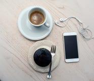 Vista superiore di caffè, delle cuffie, del cellulare e del dolce sulla tavola di legno Fotografia Stock Libera da Diritti