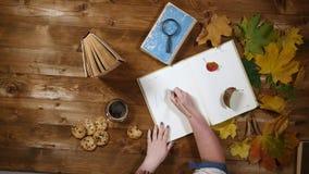 Vista superiore di concetto di autunno Libri, foglie di acero, tè sulla vecchia tavola di legno Note di scrittura della donna nel video d archivio