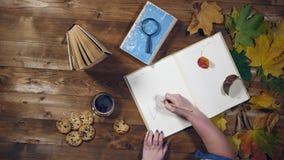 Vista superiore di concetto di autunno Libri, foglie di acero, tè sulla vecchia tavola di legno Note di scrittura della donna nel archivi video