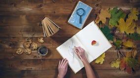 Vista superiore di concetto di autunno Libri, foglie di acero, tè sulla vecchia tavola di legno Note di scrittura della donna nel Immagine Stock Libera da Diritti