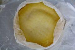 Vista superiore di formaggio rotondo avvolta in garza grezza fotografia stock