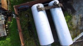 Vista superiore di grandi cisterne d'argento, bacino petrolifero al deposito di stoccaggio di petrolio sul fondo dell'erba verde  archivi video