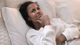 Vista superiore di pensiero della donna africana giovane che si situa a letto, confrontante le idee archivi video