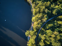 Vista superiore di piccolo lago e degli alberi verdi intorno con un piccolo percorso o via Immagine Stock