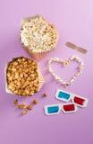 Vista superiore di popcorn con il simbolo del cuore e di vetri 3D con i biglietti del cinema Fotografia Stock