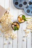 Vista superiore di popcorn con tè ghiacciato in vetri e nelle bobine di film sulla tavola, Fotografia Stock