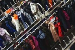 Vista superiore di tantissimi vestiti differenti sui ganci Fuoco selettivo Immagini Stock Libere da Diritti
