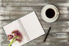 Vista superiore di un diario o un taccuino, matita e caffè e un fiore porpora su una tavola di legno grigia Progettazione piana fotografia stock libera da diritti