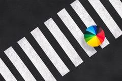 Vista superiore di un ombrello dell'arcobaleno su un attraversamento pedonale Immagine Stock