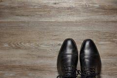 Vista superiore di un paio delle scarpe degli uomini su un pavimento di legno fotografia stock