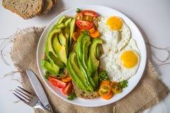 Vista superiore di un piatto con i panini dell'avocado con due uova sul piatto e vegetbles fotografia stock