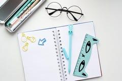 Vista superiore di un taccuino in bianco aperto con una penna a forma di lepre blu, un righello con un gatto, vetri immagine stock