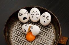 Vista superiore di un uovo rotto e dell'uovo con i fronti spaventati in una padella Fotografia Stock Libera da Diritti