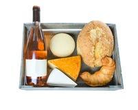 Vista superiore di una cassa di legno con la vite, il formaggio e la pasticceria su fondo bianco fotografia stock
