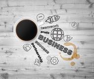 Vista superiore di una tazza di caffè e delle icone nere di affari che simbolizza un successo nell'affare Fotografia Stock