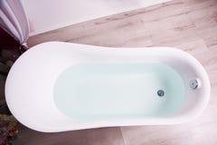 Vista superiore di una vasca da bagno bianca riempita di chiara acqua che sta su un pavimento di legno marrone chiaro del bagno immagine stock