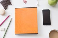 Vista superiore di uno scrittorio funzionante con il taccuino arancio Immagini Stock Libere da Diritti