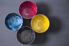 Vista superiore di vecchie latte della pittura di CMYK su fondo scuro BAC variopinto Fotografia Stock