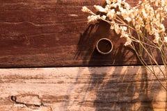 Vista superiore e tono caldo l'anello messo accanto al fiore bianco tutto del mazzo di questo che mette sopra vecchio di legno è  Fotografia Stock