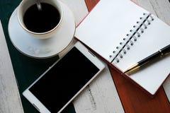 Vista superiore il telefono cellulare, tazza di caffè con caffè, penna ha messo sopra il nessun superiore Immagini Stock