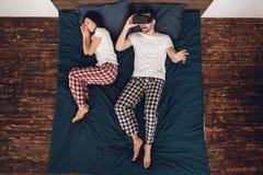 Vista superiore L'uomo adulto felice in vetri di realtà virtuale si trova sul letto accanto alla donna addormentata fotografie stock libere da diritti