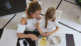 Vista superiore La donna mescola gli ingredienti per il pan di Spagna, lei è aiutata da una piccola figlia Della bambina uova del stock footage