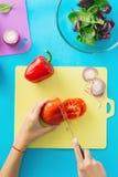 Vista superiore, le mani delle donne piane di disposizione che cucinano insalata Immagine Stock