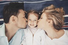 Vista superiore Madre e padre Kisses Happy Daughter fotografia stock libera da diritti