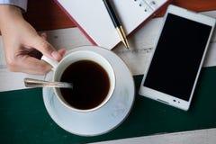 Vista superiore mano della tazza di caffè della tenuta dell'uomo d'affari con caffè e Immagini Stock