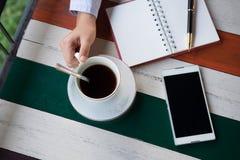 Vista superiore mano della tazza di caffè della tenuta dell'uomo d'affari con caffè e Immagine Stock Libera da Diritti