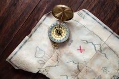 Vista superiore per simulare la mappa d'annata dei pirati dell'isola del tesoro con la croce rossa sulla tavola di legno Fotografie Stock