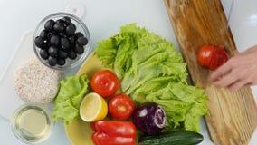Vista superiore Pomodoro di taglio della donna su un tavolo da cucina affettatura delle verdure su un tagliere di legno 4K stock footage
